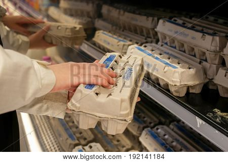 Coquitlam, BC, Canada - May 02, 2017 : Woman selecting eggs in grocery store produce department