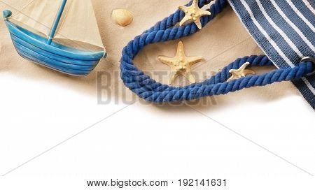 Composition with sand, small ship and beach bag on white background. Concept of travel and vacation