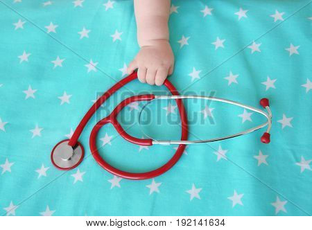 Baby hand and stethoscope on bedsheet. Baby health concept