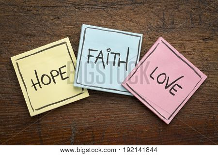 faith, love and hope - colorful sticky notes on rustic wood