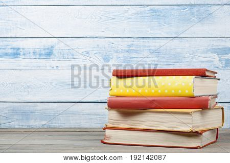 Stack of colorful books on wooden background. Copy space for text. Back to school. Education concept.