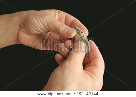 Man making cigarette with weed bud on black background, closeup