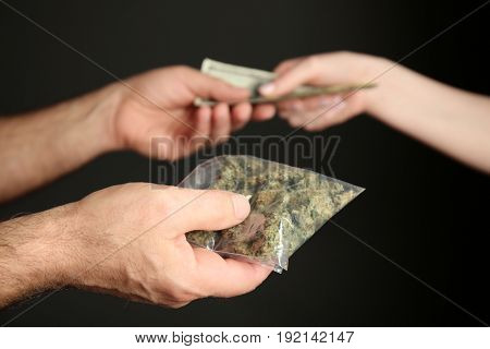 Man buying weed buds on black background, closeup