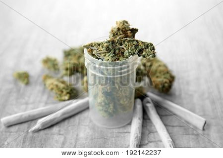Weed buds in plastic container with cigarettes on grey background