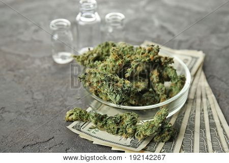 Heap of weed buds in Petri dish with  money on grey background