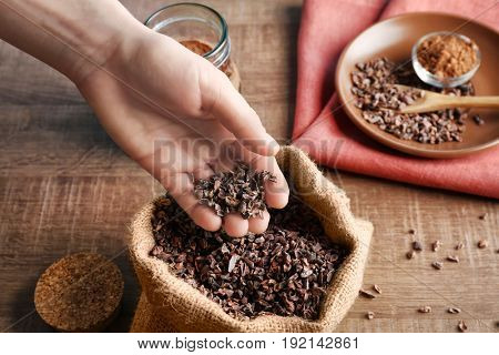 Human hand taking pile of cocoa nibs from bag