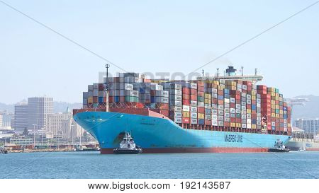 Oakland CA - June 06 2017: Multiple tugboats assist cargo ship GUDRUN MAERSK to maneuver into the Port of Oakland the fifth busiest port in the United States.