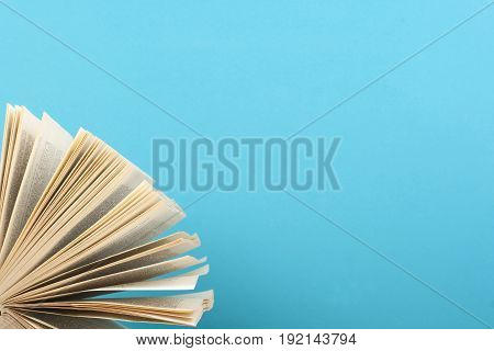 Open book on the background of blue wall. Copy space for text