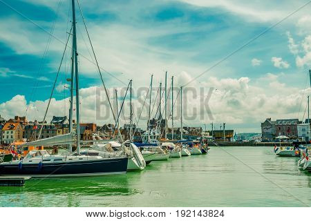 Yachts moored at quay port of Dieppe France. Concepts of success leisure holiday rich tourism luxury lifestyle. Sunny Summer blue sky. Toned