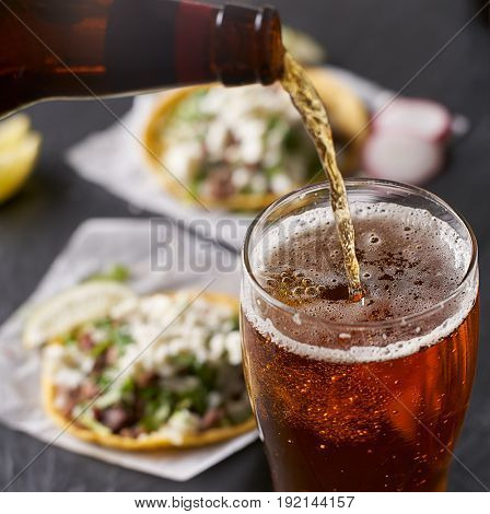 pouring beer in front of mexican tacos