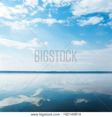 deep blue sky with clouds over river and reflection of it