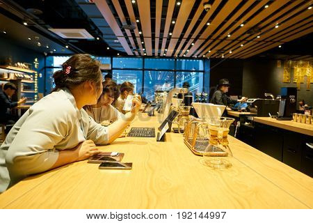 SEOUL, SOUTH KOREA - CIRCA MAY, 2017: people at Starbucks in Seoul. Starbucks Corporation is an American coffee company and coffeehouse chain.