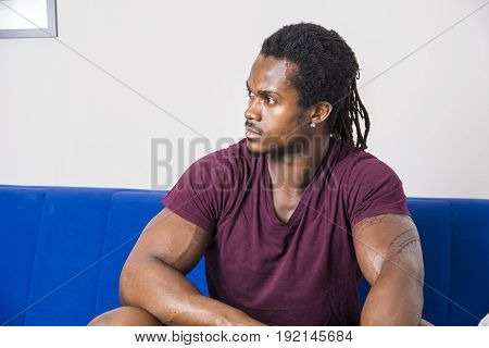 Handsome muscular black man sitting on couch at home, looking confident to a side