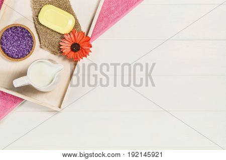 Spa frame top view. Background on white wooden table or floor with copy space. Wellness salon concept with lay flat beauty accessories.