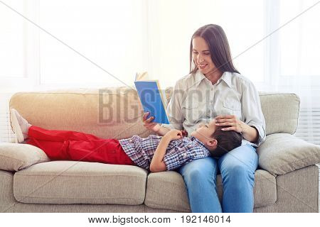 Mid shot of carrying mother sitting with son reading story indoors