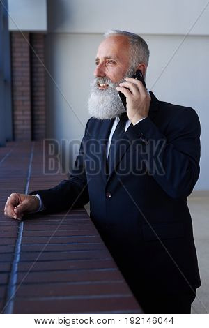 Vertical of good-looking gentleman talking on phone while leaning on sill