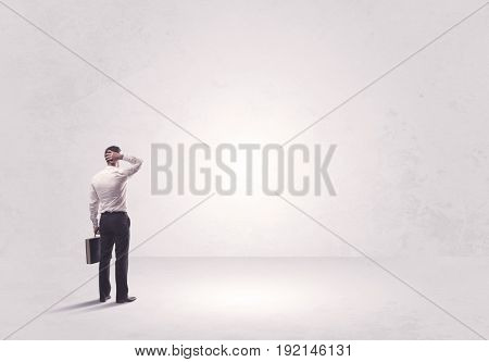 Elegant business person standing with his back looking at big empty white space concept