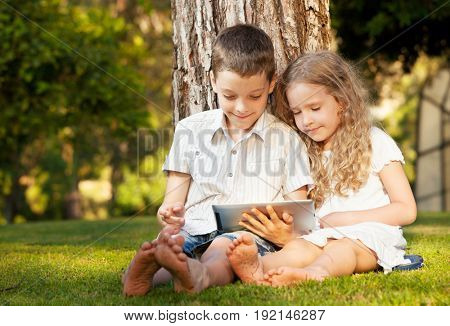 Girl and boy on grass with computer