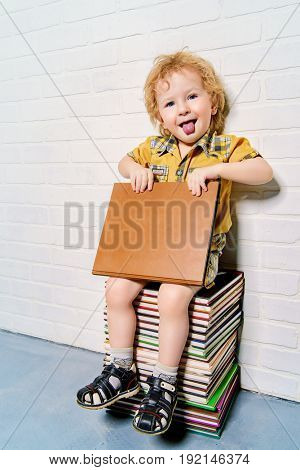 Cute little boy sitting on a stack of books with a book. Educational concept.