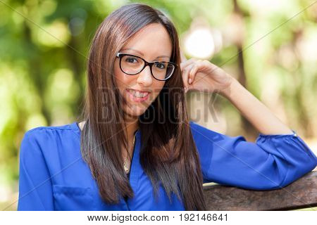Portrait of a young smiling woman in a park