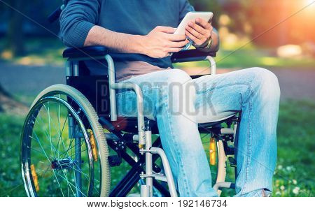 Man using a tablet on his wheelchair, filtered image