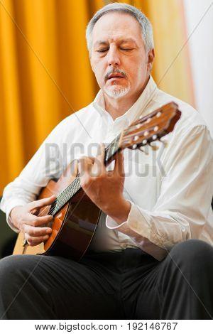 Mature man playing a classical guitar