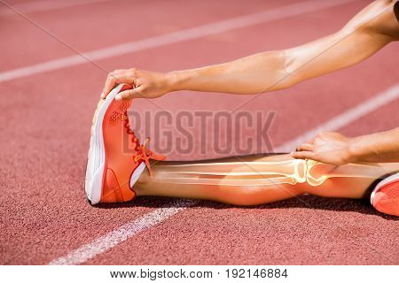 Low section of female athlete stretching on track during sunny day