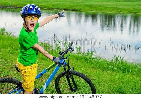 Cute excited boy is riding his bike. Happy summer holidays. Competition.