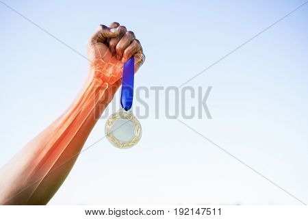Cropped image of sportsperson holding gold medal against clear sky