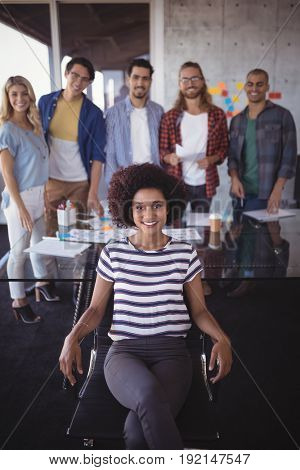 Portrait of confident businesswoman with creative team in office
