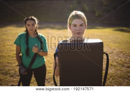 Portrait of women holding boxing equipment during obstacle course in boot camp