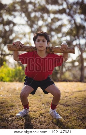 Portrait boy exercising with log during obstacle course in boot camp