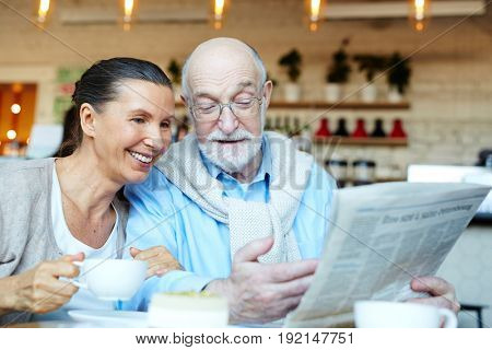 Mature man showing his wife latest news by cup of tea