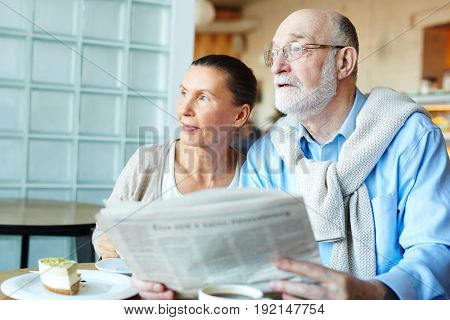 Modern couple of seniors with newspaper sitting in cafeteria