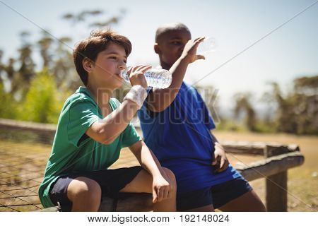 Boys drinking water after workout during obstacle course in boot camp