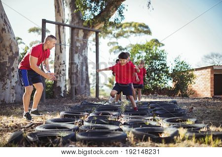 Trainer instructing kids during tyres obstacle course training in the boot camp