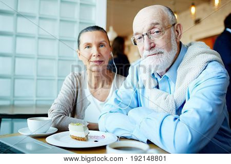Affectionate couple listening to music in cafe