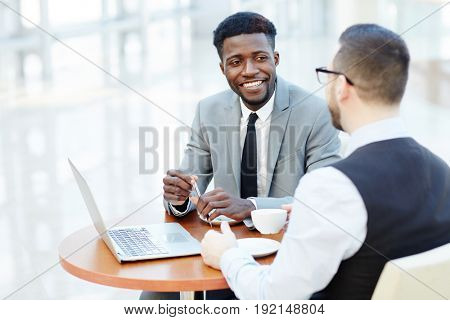 Portrait of successful African-American businessman smiling while discussing deal with partner during meeting at coffee break