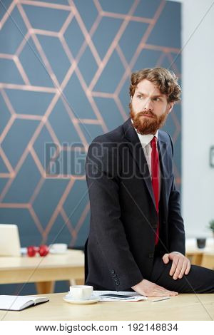 Serious bearded man in suit siting on desk