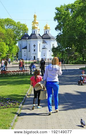Chernihiv / Ukraine. 06 May 2017: happy mother walks with her little daughters in the city park. 06 May 2017 in Chernihiv / Ukraine.