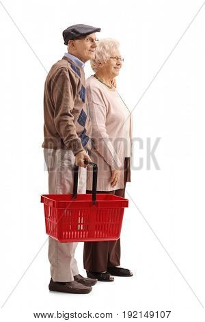 Full length profile shot of a senior couple with an empty shopping basket isolated on white background