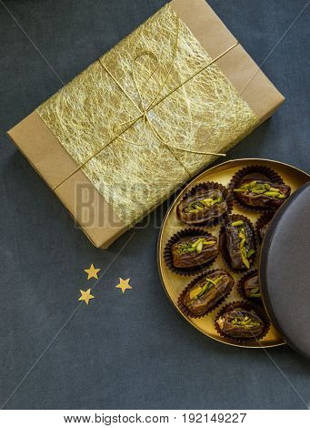 An elegant golden gift box and fine quality arabian dates stuffed with pistachio nuts. Gift and sweets on the occasion of Eid celebration.