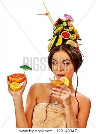 Girl drinking fruit cocktail on summer party. Woman with fresh fruits hairstyle and bare back hold halves of grapefruit with cocktail umbrella. Woman is resting in bar abroad concept on isolated.