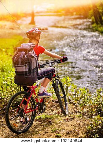 Woman traveling bicycle in summer park. Early morning with first rays of sun and fog. Cycling girl overcomes river. Sport trip is good for health. Back view. Color tone on shiny sunlight background.
