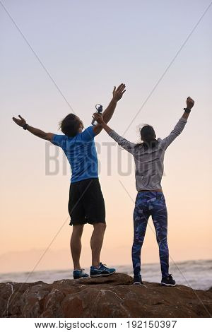Backview of active healthy couple raising their arms in celebration satisfaction after completing their grueling exercise workout run