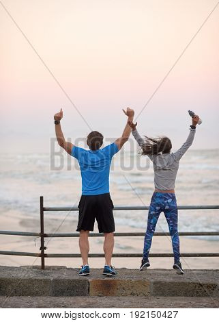 Happy couple jump and raise arms in air after completing their run exercise, celebrate accomplishment