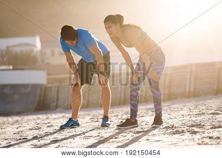 Fit athletic couple resting catching their breath after intense workout exercise on beach sand