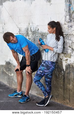 Fit athletic couple resting drinking water after their run