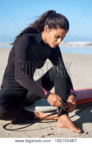 Surfer in wetsuit sitting on surfboard tying leash to ankle before hitting the waves