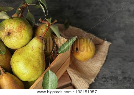 Fresh pears in crate on grey background